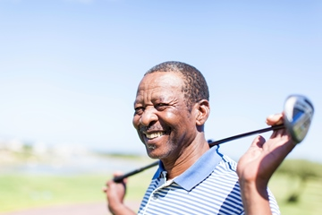 African senior golfer holding his club with a smile at Langebaan's golf course in Western Cape, South Africa.