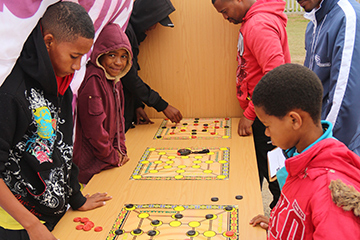 Children playing Morabaraba, a boardgame in some ways resembling chess or checkers