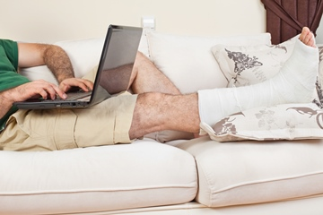 A middle aged man sitting on the couch with a broken leg and a laptop working from home