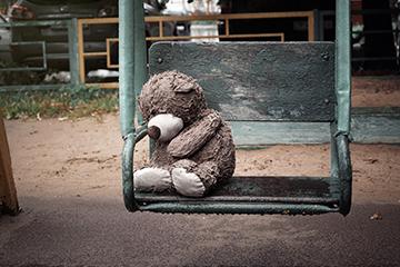 Wet miserable teddy bear left behind on a swing