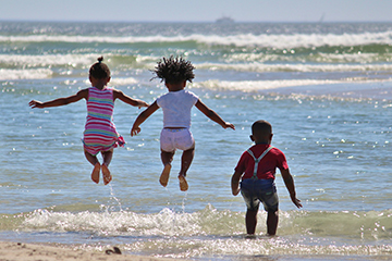 children jumping into the sea