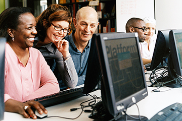 adults looking at computer screen in computer lab