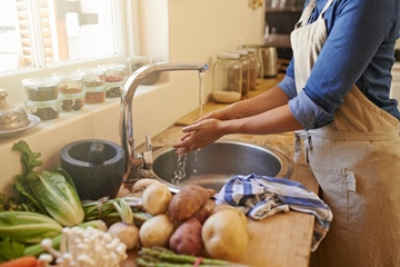 Cropped picture of an unrecognizable woman washing her hands in the kitchen sink. She's about to prepare food.
