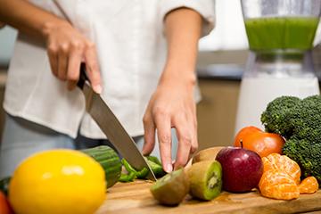 Women cutting vegetables while preparing food.