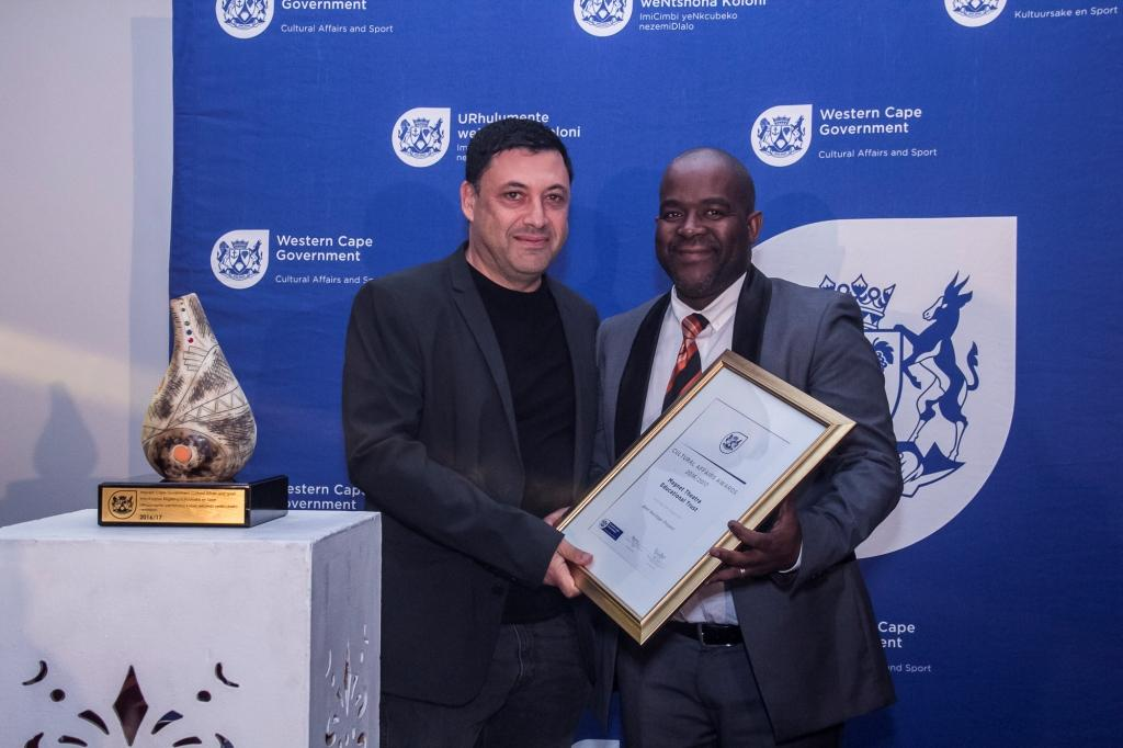 Director Mxolisi Dlamuka presents an award to the Magnet Theatre Education Trust at the 2016/17 Cultural Affairs Awards Ceremony