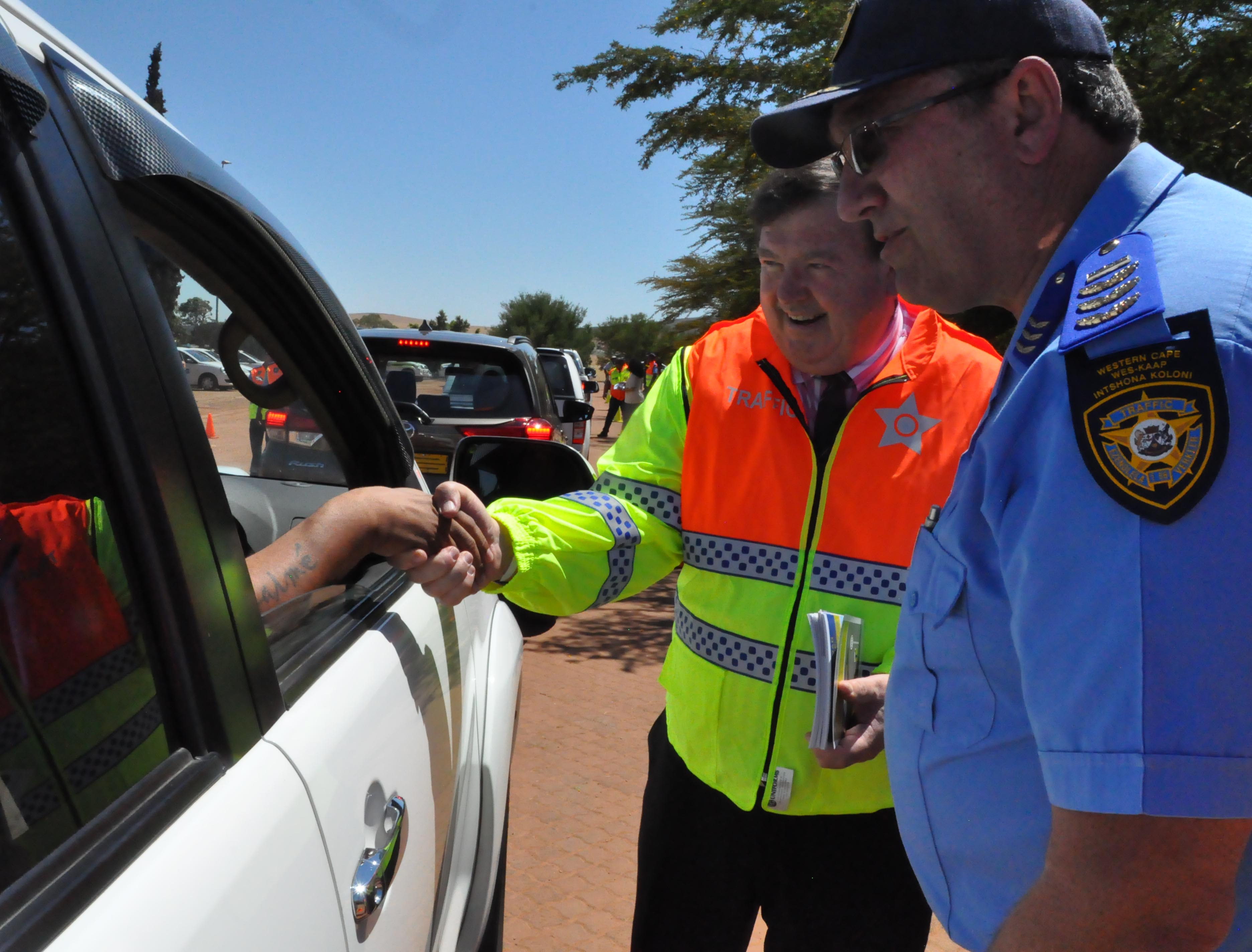 Minister Donald Grant and Vredenburg Traffic Chief Desmond Payton interact with a motorist.