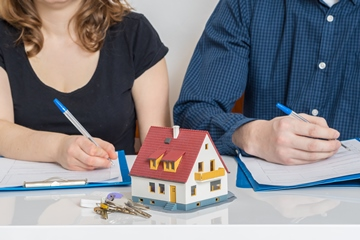 Man and woman sitting at a table signing divorce agreement and dividing property.