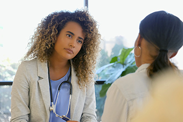 Female doctor listening to patient talking while she's talking.