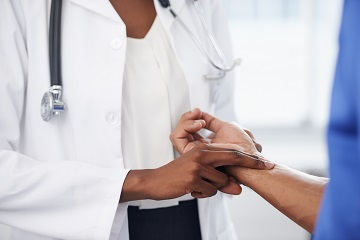 Dr checking a man's pulse