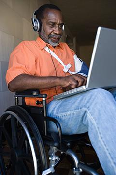 elderly man in wheelchair with a laptop
