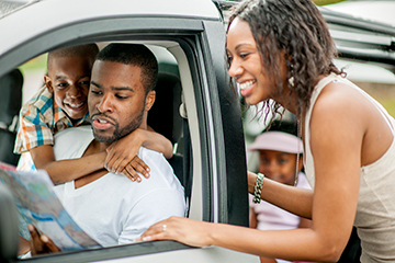 Family traveling by car looking at a map