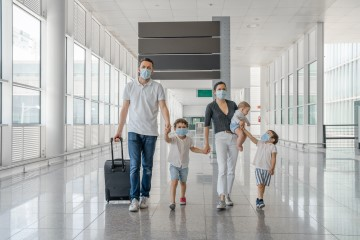Family of 5 going on holiday, walking at the airport