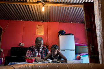 Father reading with his daughter at home after work.