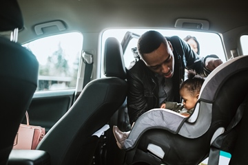 Father buckles her daughter in car seat
