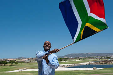 Man waving the South African flag on Freedom Day.