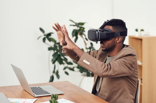 guy_sitting_at_a_desk_with_virtual_reality_glasses_on.png