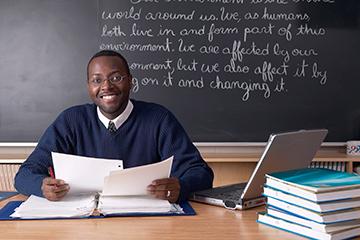happy-male-teacher-at-desk