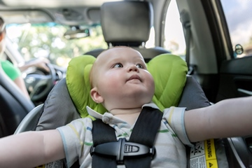 happy baby boy secure in rear facing baby car seat. Mom driving in the background.