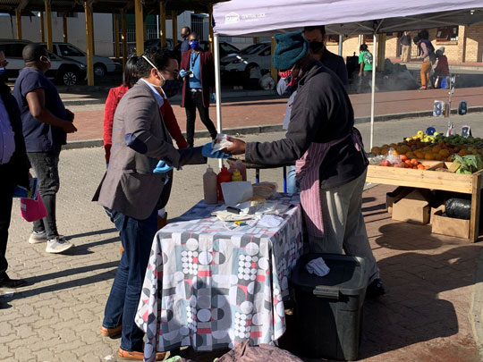 Minister Simmers engaging residents in Pacaltsdorp and purchasing a boerewors roll from a vendor in Thembalethu