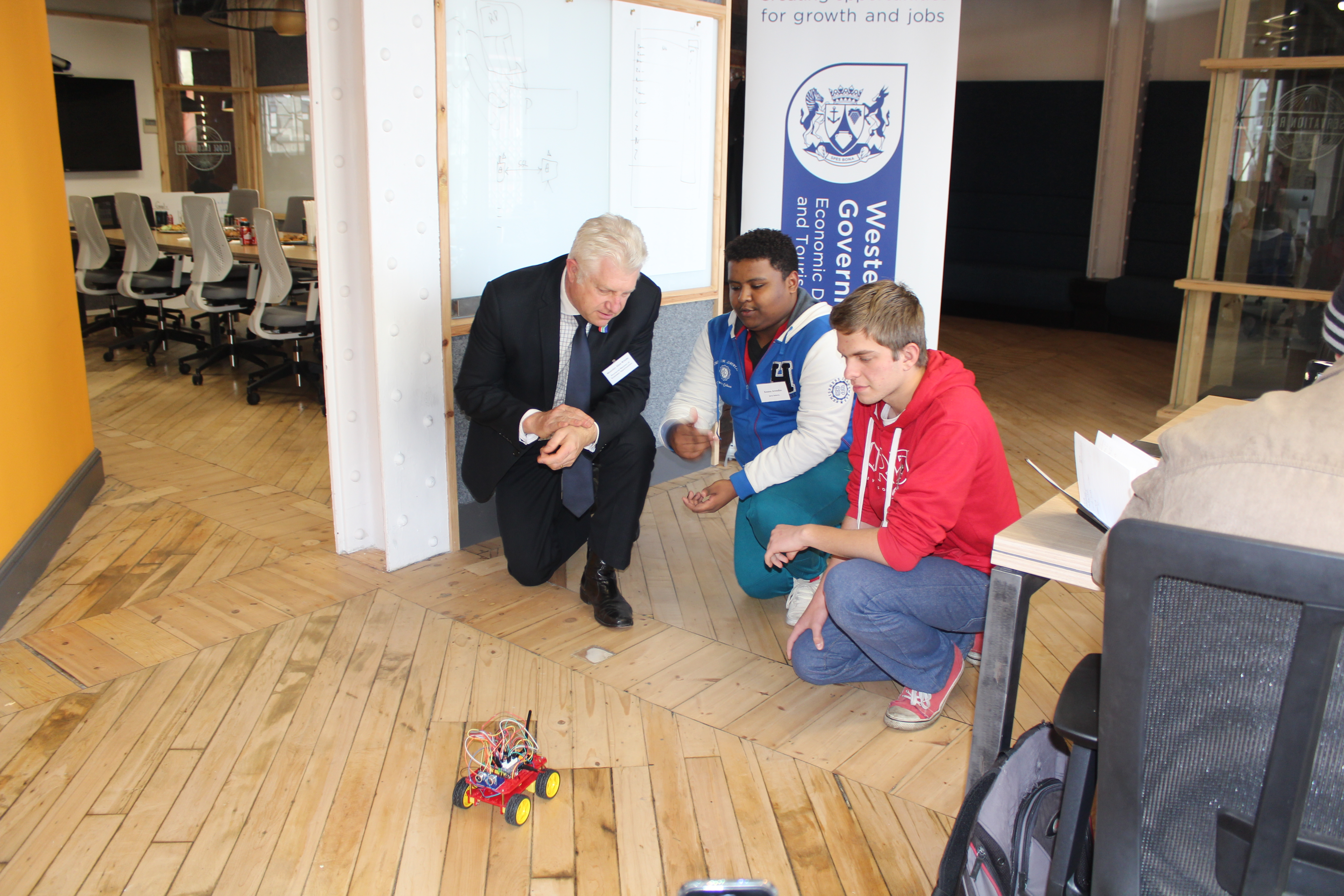 Minister Winde watches on as Keanu Arendze and Rossouw Binedell demonstrate one of their innovations.