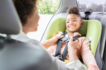 little girl smiles at her mother as she buckles her car seat harness