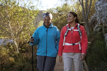 elderly woman hiking on a mountain with young woman