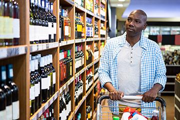 Young man walking through the liquor aisle