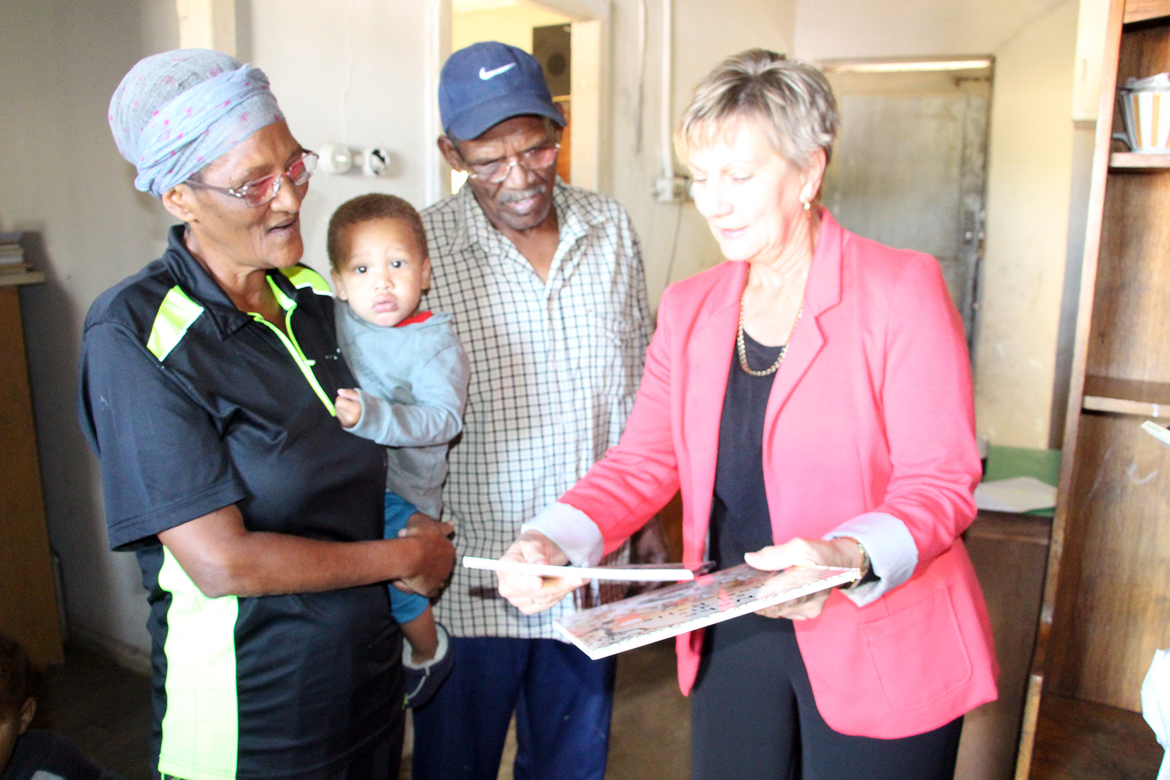 Minister Anroux Marais handing over books to the Cupido family