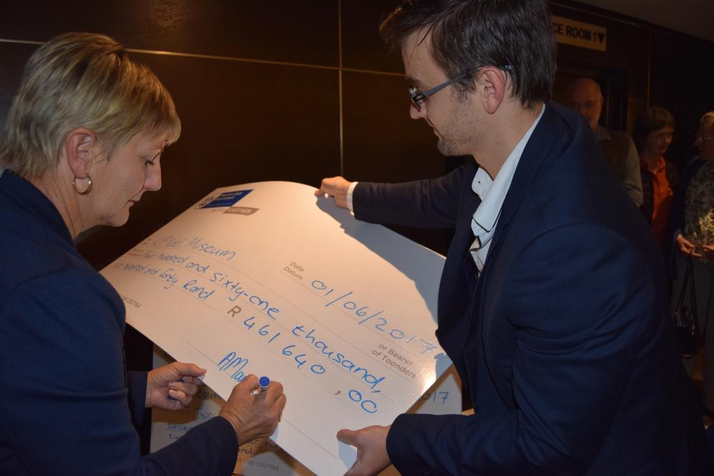 Minister Anroux Marais signs the ceremonial cheque for CP Nel Museum at the Museum Symposium in Cape Town
