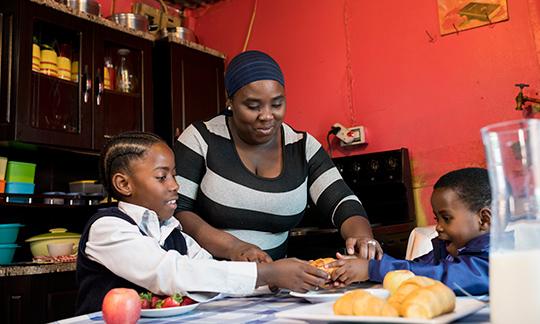 Mom and two children preparing breakfast.