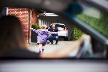 Blurred out mommy in car drops daughter at her daddy's house. Daughter running to daddy with his arms wide open and smiling.