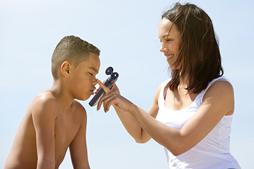 mother-putting-sunblock-on-her-son