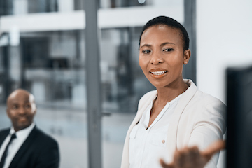 An african lady standing in a boardroom doing a presentation