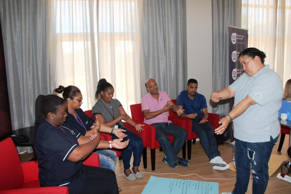 Nurses and physiotherapists learning how to sign some common phrases to assist them with communicating with Deaf patients