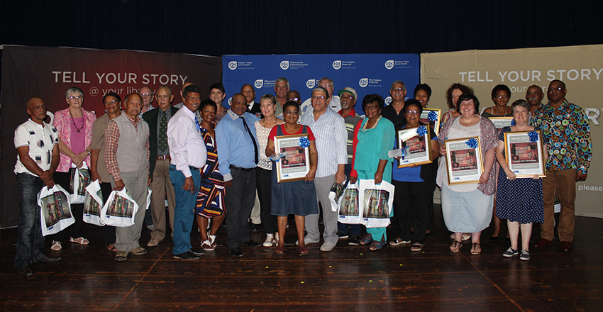 Officials from public libraries in the Mossel Bay area and the storytellers who participated in the initiative receive framed posters.