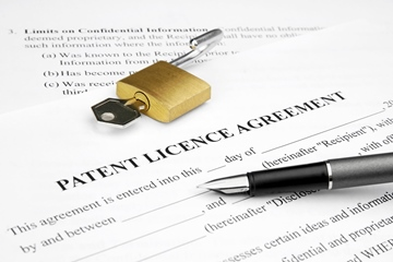 Patent license agreement form with pen and open lock on top of it