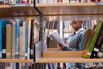 School learner reading a book in the library