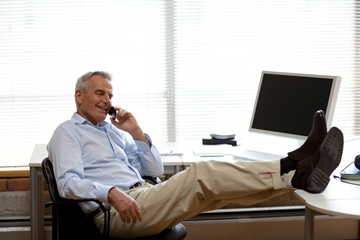 Senior businessman on the phone at his office with his feet on the desk