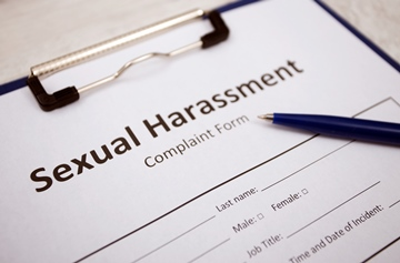 A close up of a sexual harassment complaint form on a desk with a pen
