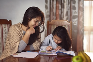 Shot of a mother helping her daughter with school work at home