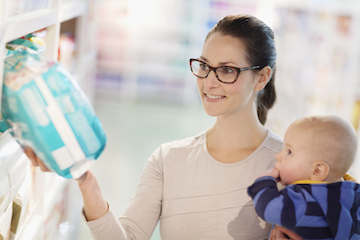 Single mother holding baby shopping for nappies at the supermarket