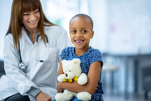 smiling child cancer patient with toy teddy bear in her arms