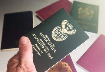 A hand holding a South African passport