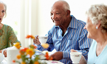 Elderly man and women enjoying tea together.