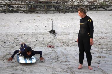 9Miles facilitator, Nathaniel Stemmet, teaching Minister Marais the basics of surfing.