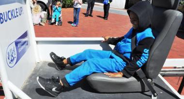 A boy test the seatbelt convincer.