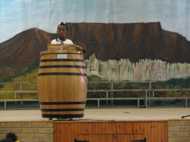 A participant presents her story against the painted backdrop of Table Mountain