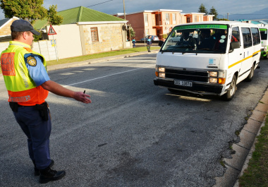 A provincial traffic official inspects the roadworthiness of a minibus taxi at the school.