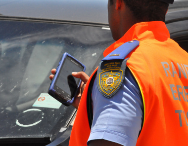 A traffic officer uses a hand-held device.