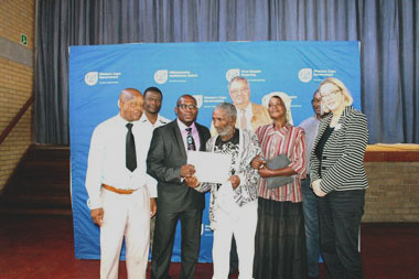 80 Year old beneficiary, Mr Wildschut (pictured centre), receives the title deed to his home in Delft from Western Cape Minister of Human Settlements, Bonginkosi Madikizela